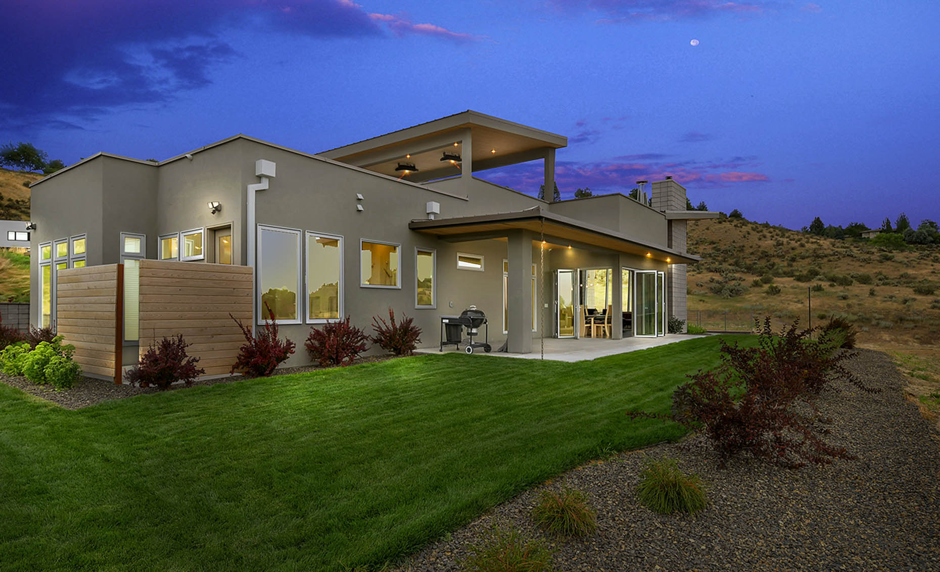 The Nature View Custom Home Backyard Exterior at Dusk
