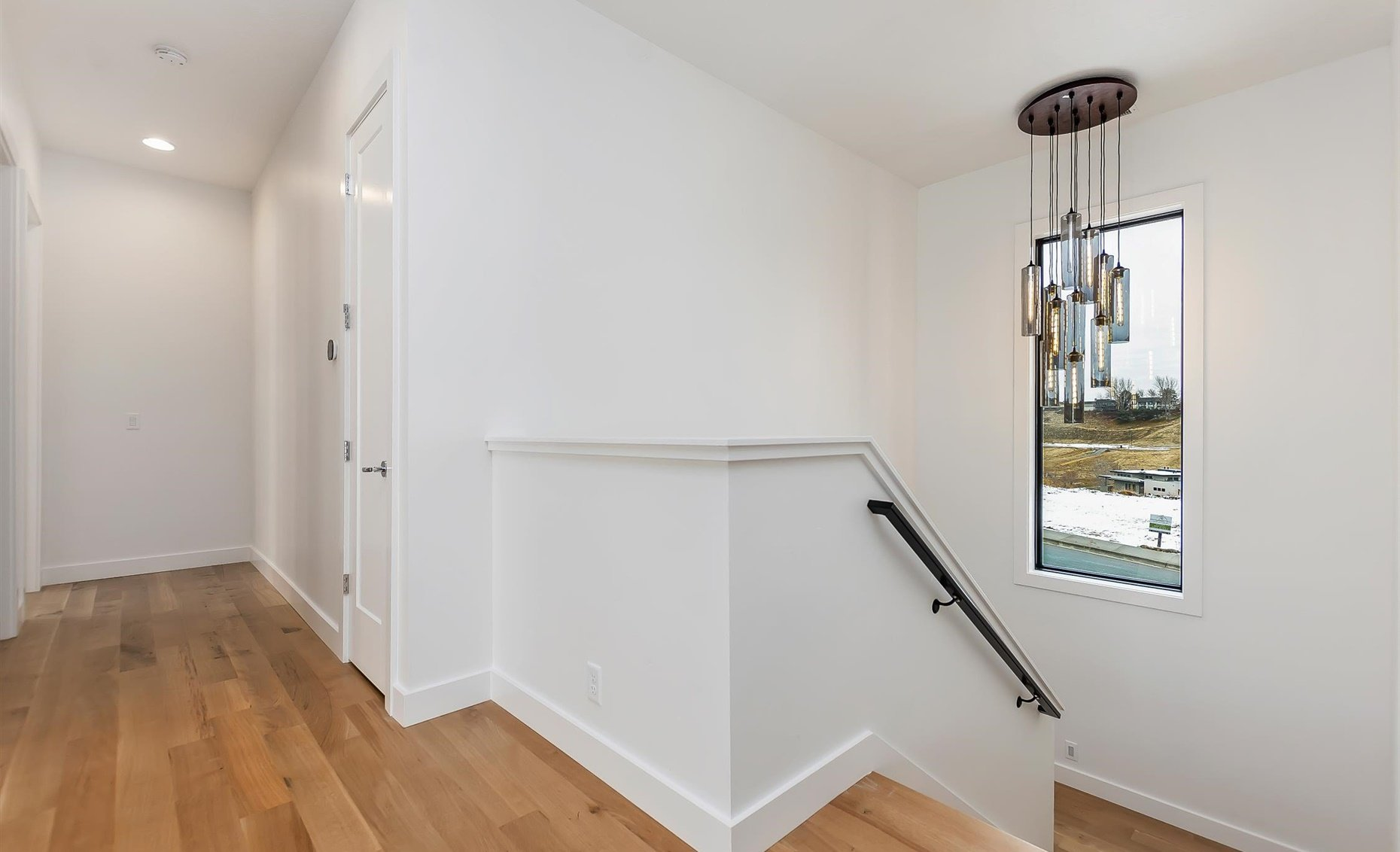 East Highland | Interior view of hallway, staircase, and a modern chandelier